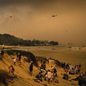 Tourists in Lake Conjola, a popular holiday destination in Australia, take refuge on a beach from wildfires on Tuesday, Dec. 31, 2019.  This fire season has been one of the worst in Australia's history, with at least 15 people killed, hundreds of homes destroyed and millions of acres burned.  (Matthew Abbott/The New York Times)